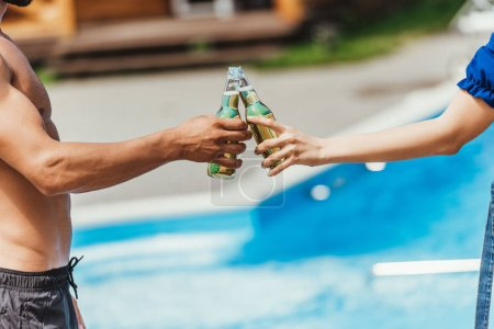 cropped view of couple clinking with bottles of beer at poolside