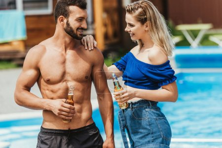 Photo for Young couple talking and  holing bottles of beer at poolside - Royalty Free Image