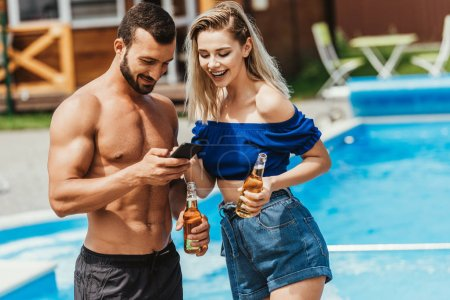 Photo for Couple using smartphone and holding bottles of beer at poolside - Royalty Free Image