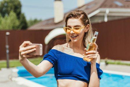happy attractive girl taking selfie with bottle of beer on smartphone