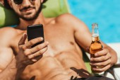 cropped view of man using smartphone and holding bottle of beer