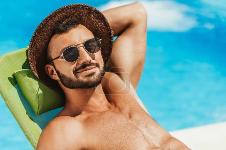 Photo for Handsome man in sunglasses and straw hat relaxing on sunbed at swimming pool - Royalty Free Image