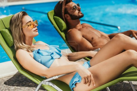 beautiful young couple sunbathing on sunbeds at poolside