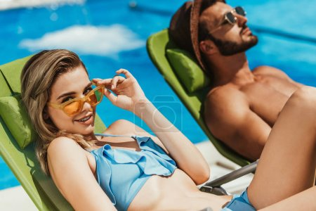 young couple in sunglasses relaxing on sunbeds at poolside