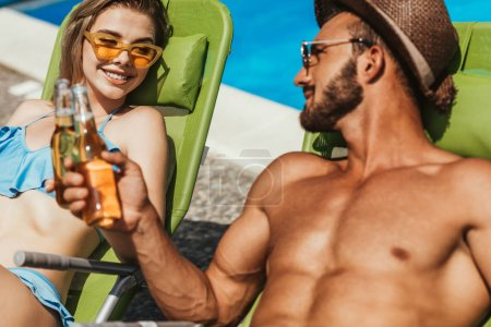 couple clinking with bottles of beer while resting on sunbeds at poolside
