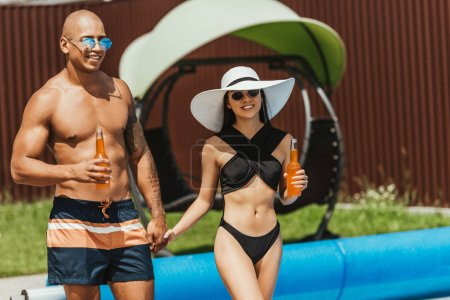 multiethnic couple with bottles of beer and holding hands at poolside