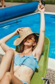 beautiful woman with straw hat relaxing on sunbed at poolside