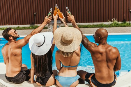 back view of multicultural friends in swimsuits clinking with bottles of beer near swimming pool