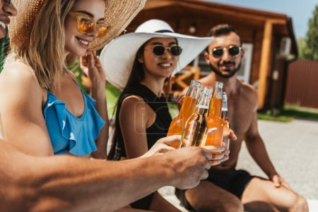 young multicultural people clinking with bottles on beer in summer