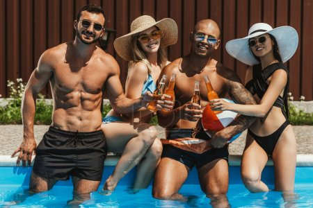 young happy multicultural friends clinking with bottles of beer in swimming pool