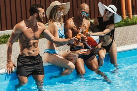 young multicultural friends clinking with bottles of beer at poolside