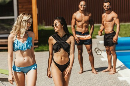 Photo for Multiethnic beautiful girls in swimsuits and sunglasses walking at poolside with boyfriends behind - Royalty Free Image
