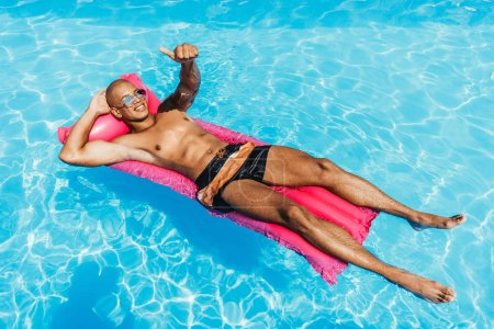 african american man showing thumb up while sunbathing on inflatable mattress in swimming pool