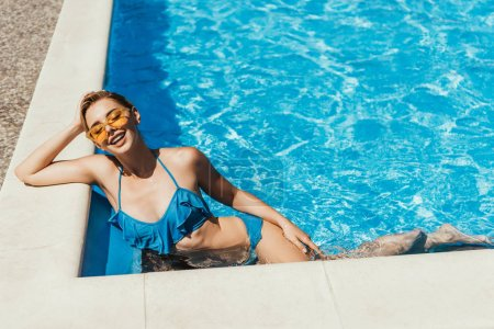 beautiful smiling woman in blue swimsuit sunbathing in swimming pool