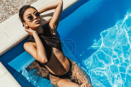 beautiful asian girl in swimsuit and sunglasses resting in swimming pool