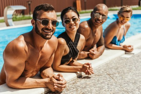 multiethnic friends in swimsuits and sunglasses resting in swimming pool