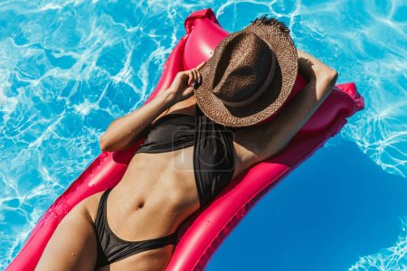 slim girl in swimsuit and straw hat sunbathing on inflatable mattress in swimming pool