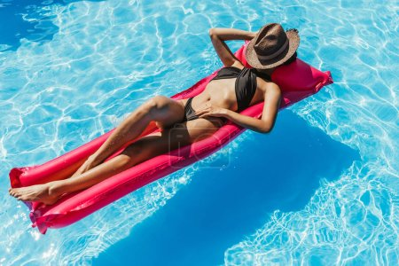Photo for Young woman in black swimsuit and straw hat sunbathing on pink inflatable mattress in swimming pool - Royalty Free Image