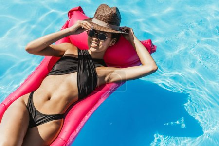 attractive asian woman in swimsuit and straw hat relaxing on pink inflatable mattress in water
