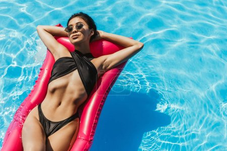 top view of asian girl in swimsuit and sunglasses sunbathing on inflatable mattress in water