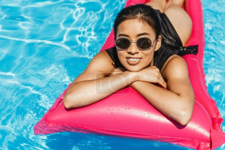 asian girl in swimsuit and sunglasses sunbathing on inflatable mattress in swimming pool