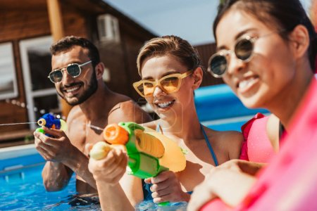 multiethnic people in sunglasses playing with water guns in swimming pool
