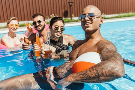 multiethnic friends with bottles of beer relaxing in water in swimming pool
