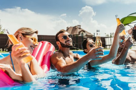 multicultural friends with bottles of beer in swimming pool with inflatable mattress