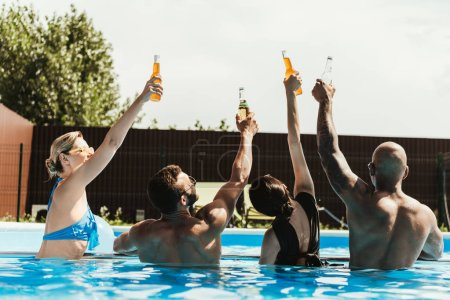 back view of multicultural friends rising up bottles of beer in swimming pool