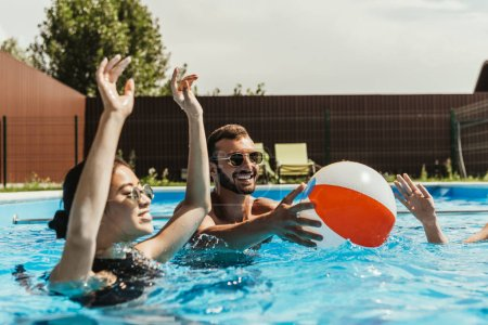 Photo for Multiethnic friends playing with beach ball in swimming pool - Royalty Free Image