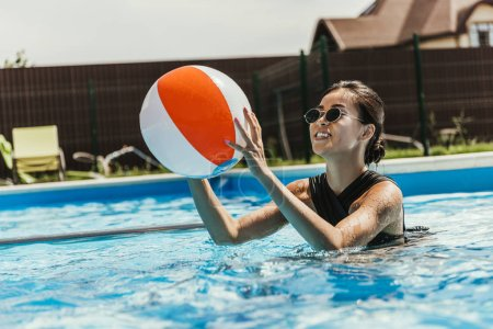 happy asian girl in swimsuit and sunglasses playing with beach ball in swimming pool