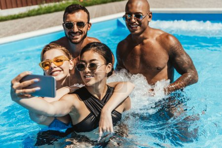 multiethnic friends in sunglasses taking selfie on smartphone in swimming pool