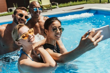 multicultural couples in sunglasses taking selfie on smartphone in swimming pool