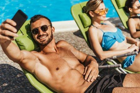 man taking selfie with girls sunbathing on sunbeds at poolside