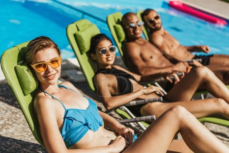 smiling multicultural friends in swimsuits sunbathing on sunbeds at swimming pool