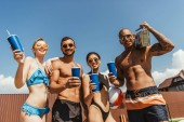 cheerful multicultural people with drinks and retro boombox