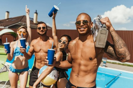 smiling multiethnic friends with drinks and retro boombox at poolside