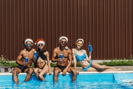 happy multicultural friends in santa hats with drinks relaxing at swimming pool