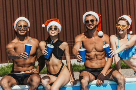 smiling multicultural friends in santa hats with drinks