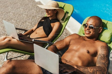 interracial couple relaxing on sunbeds and using laptops at poolside