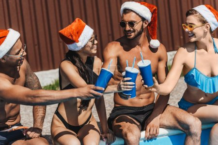 multiethnic friends in santa hats with drinks sitting at poolside