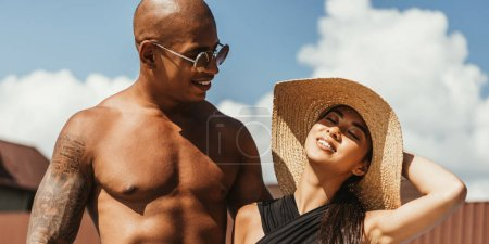 young multicultural couple in sunglasses and straw hat with sky on background
