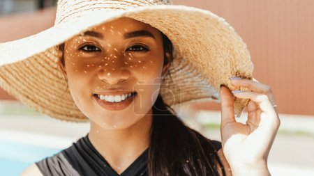 smiling asian young woman in swimsuit and straw hat