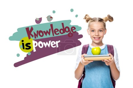 """Photo for Schoolchild holding apple on books isolated on white, with """"knowledge is power"""" lettering - Royalty Free Image"""