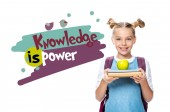 "schoolchild holding apple on books isolated on white, with ""knowledge is power"" lettering"