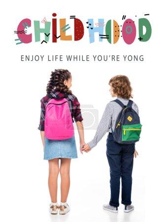 """Photo pour Vue arrière de camarades de classe avec des sacs à dos tenant les mains isolées sur blanc, avec lettrage """"enfance"""" - image libre de droit"""