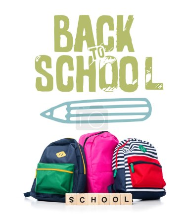 "three colored schoolbags and wooden cubes with word school isolated on white, with pencil and ""back to school"" lettering"