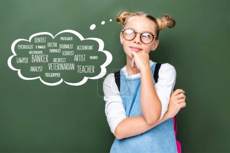Photo pour Cher écolier en lunettes regardant vers le haut près du tableau noir avec différentes professions dans la bulle de la parole - image libre de droit