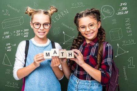 Photo pour Écoliers tenant des cubes en bois avec math mot près de tableau noir avec des symboles mathématiques - image libre de droit