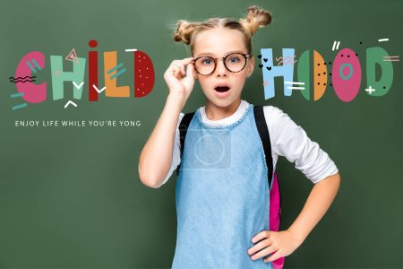 """shocked schoolchild touching glasses and looking at camera near blackboard, with """"childhood"""" lettering"""